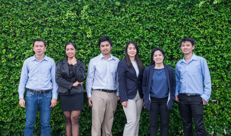 Team of Asian business man and woman looking at camera with smiling face outside office at green leaf wall