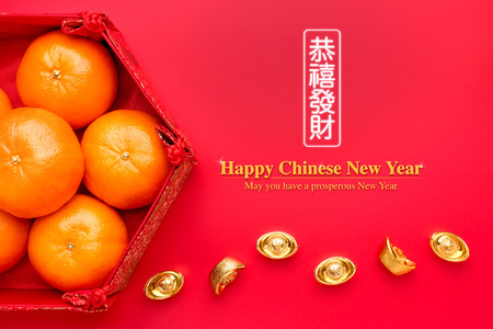 Photo pour Group of orange tangerine in Chinese pattern tray with gold ingots on red table.Chinese Language on ingot mean wealthy and lable mean May you have a prosperous New Year - image libre de droit