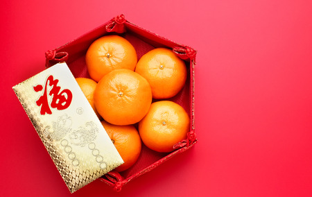 Foto de Group of orange tangerine in Chinese pattern tray and envelope packet ang pow on red table top. Chinese new year concep.Chinese Language on envelop is happiness,on ingot is wealthy - Imagen libre de derechos