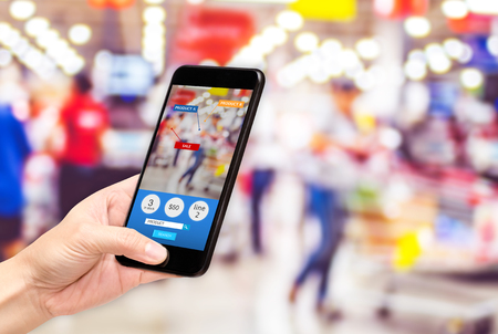 Photo pour Hand hold mobile phone and using augmented reality ( AR ) app for see promotion sale in supermarket store,Digital lifestyle Technology concept - image libre de droit