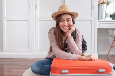 Foto de Young asian woman traveler packing stuff in orange suitcase prepare for holiday vacation at home.backpacker travel concept - Imagen libre de derechos