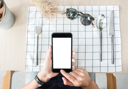 woman use mobile phone apps at restaurant table.Mobile payment.Digital leisure lifestyle.mock up template for display of content.top view angle.clipping path on screen