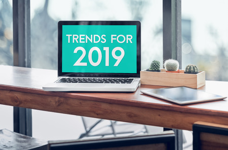 Photo for Trends for 2019 word in laptop computer screen with tablet on wood stood table in at window with blur background,Digital Business or marketing trending - Royalty Free Image