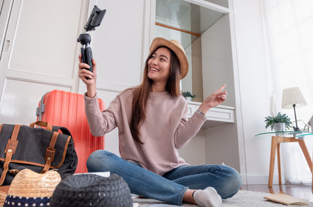 Photo for Asian young female blogger recording vlog video with mobile phone live streaming when travel.online influencer on social media viral concept - Royalty Free Image
