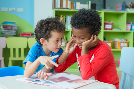 Photo pour Two boy kid sit on table and coloring in book  in preschool library,Kindergarten school education concept. - image libre de droit