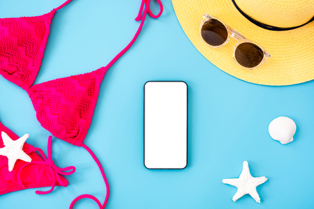summer blue banner with yellow hat ,pink bikini,mobile ,sunglasses and seashell on blue background top view mock up screen