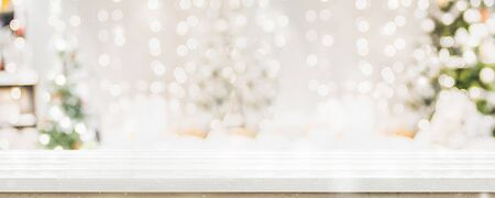 Foto de Empty white wold table top with abstract warm living room decor with christmas tree string light blur background with snow,Holiday backdrop,Mock up banner for display of advertise product - Imagen libre de derechos