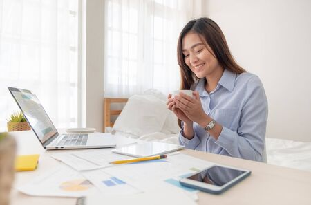 Photo pour Asian businesswoman drinking coffee and while working with laptop on table in bedroom at home.Work at home concept.work from home concept - image libre de droit