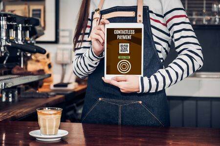 Foto de CLose up woman barista hand holding tablet with contactless payment method at counter bar in restaurant cafe.online payment - Imagen libre de derechos