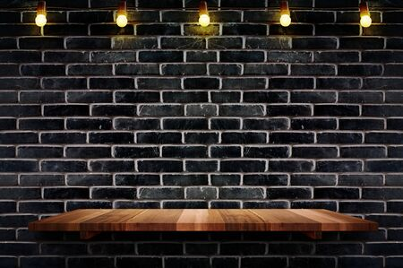 Photo pour Empty brown plank wood shelf at black brick wall background with light bulbs string,Mockup for display or montage of product or design. - image libre de droit