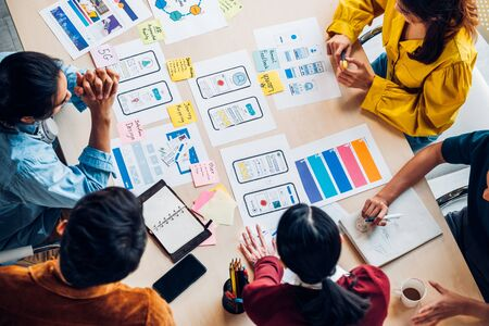 Photo pour top view asian ux developer and ui designer brainstorming about mobile app interface wireframe design on table with customer brief and color code at modern office.Creative digital development agency - image libre de droit