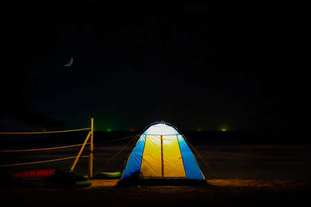 Photo for Traveling and camping concept - camp tent at night under a sky full of stars. Orange illuminated tent. Beautiful nature - field, forest, plain. Moon and moonlight - Royalty Free Image