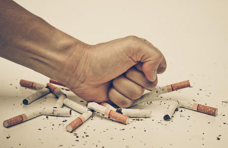 male hand destroying cigarettes - stop smoking concept