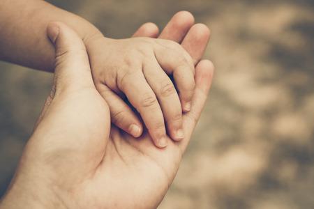 Foto de adult's hand holding a baby's hand - Imagen libre de derechos