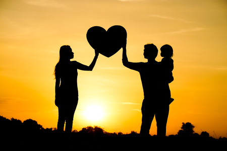 Photo pour Silhouette of a family comprising a father, mother, and a child  Family love concept - image libre de droit