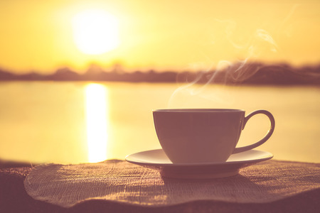 Photo for Silhouettes of sunrise morning coffee with a note and a pen - Royalty Free Image