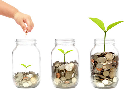Photo pour child's hand putting a golden coin into a bottle with a green plant growing on coins - image libre de droit