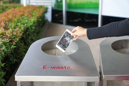 Photo pour Hand dropping an old, damaged smartphone into a bin for e-waste garbage - image libre de droit
