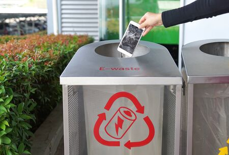 Foto per Hand dropping a smartphone into a bin for e-waste - Immagine Royalty Free