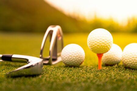 Photo pour Golf balls and golf club on green grass - image libre de droit