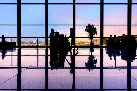 Photo pour Travelers walk through an airport terminal - image libre de droit