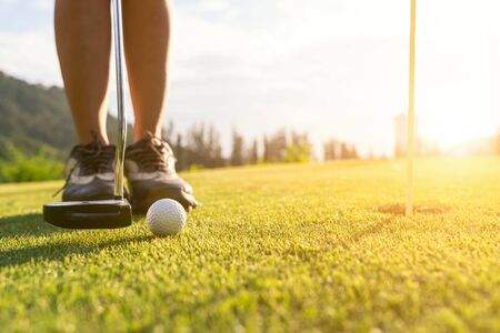 Photo pour Golf player at the putting green hitting ball into a hole - image libre de droit