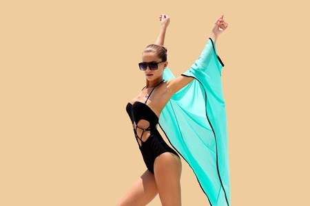 Photo for Dancing woman in black swimsuit sunglasses and turquoise beach dress poses on color background. High fashion look.  Hair up - Royalty Free Image