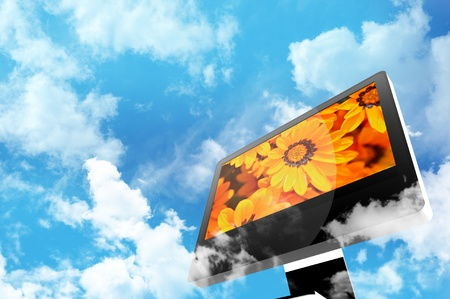 Photo pour Technology and Nature Theme. Modern Computer Display Between the Clouds. Cloudy Blue Sky. Orange Flowers on the Screen. - image libre de droit