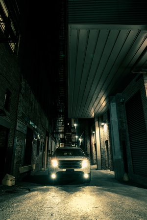 Dark Alley Drive. American City at Night. SUV on the Alley