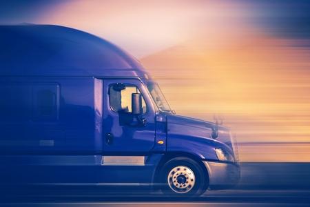 Foto de Rush Trucking. Speeding Blue Semi Truck on the American Highway. Trucking Concept. - Imagen libre de derechos
