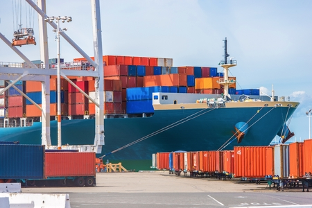 Cargo Ship Loading. Ocean Transportation Theme. Loading Cargo Containers.