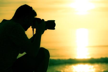 Professional Photographer on Location Closeup. Sunset Photography.