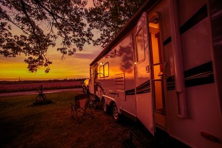 Foto de Travel Trailer Camping Spot at Scenic Sunset. Pulling Travel Trailer by Car. - Imagen libre de derechos