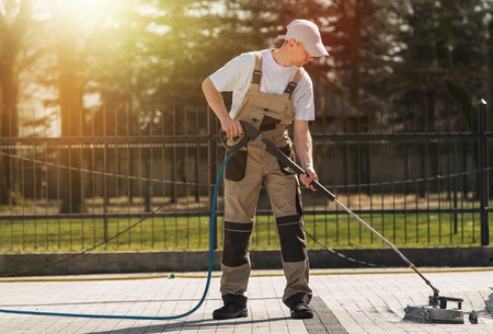 Photo for Brick Residential Roadway Cleaning by Professional Cleaning Worker. High Pressure Water Mechanical Brick and Pavements Cleaning Service Theme. - Royalty Free Image