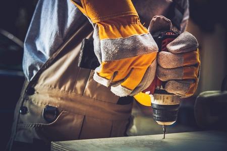 Photo pour Little of Residential Construction Works. Men Fixing Wooden Shelf with His Driller. - image libre de droit