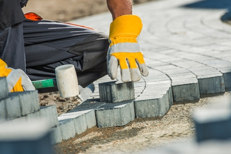 Photo for Brock Paving Closeup Photo. Construction Worker Paving Brick Pathway. - Royalty Free Image