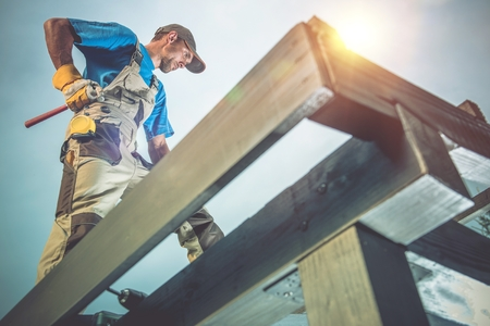 Photo for Wood Construction Works. Caucasian Worker on the Wooden Roof Construction. - Royalty Free Image
