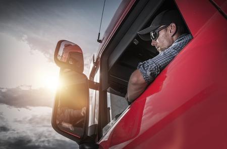Foto de Red Semi Truck. Caucasian Truck Driver Preparing For the Next Destination. - Imagen libre de derechos