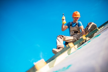 Photo pour House Roof Construction Works. Caucasian Worker in His 30s on the New Building Roof. Hammer Works. - image libre de droit