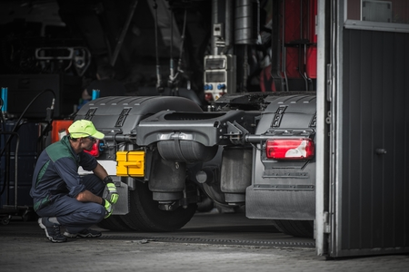 Photo pour Truck Service Technician Job. Caucasian Truck Mechanic Checking on Semi Truck Tractor. - image libre de droit