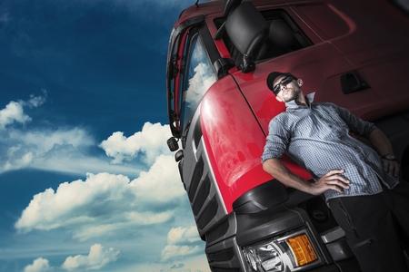 Photo pour Proud Trucker and His Truck. Caucasian Trucker with Euro Semi Tractor Closeup Photo - image libre de droit