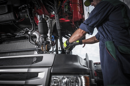 Foto de Repairing Broken Semi Truck Tractor Engine. Caucasian Trucks Mechanic.  - Imagen libre de derechos