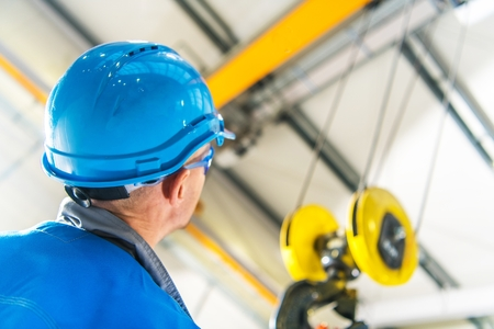 Photo for Caucasian Production Line Technician in Blue Hard Hat Checking on the Overhead Warehouse Crane Installed Right Above His Head - Royalty Free Image