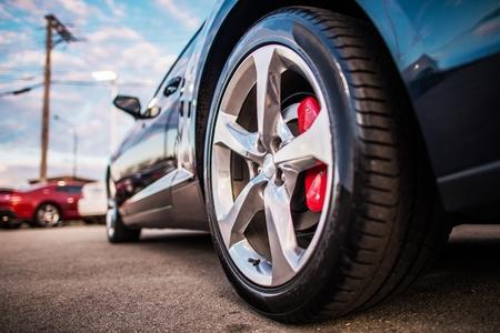 Photo pour Car on the Parking Spot. Alloy Wheel Closeup Photo. Lower Ground Level. Transportation and Automotive Theme. - image libre de droit