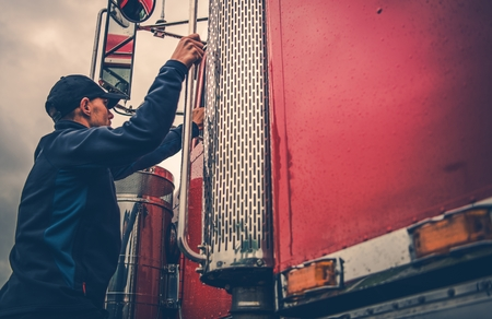 Photo pour Transportation Industry Theme. Truck Driver Getting Into Truck Time To Hit the Road with Heavy Load. - image libre de droit