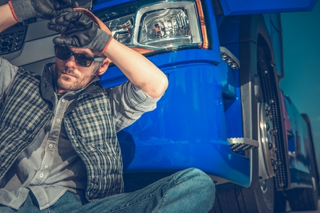 Photo pour Tired Caucasian Truck Driver in His 30s Resting in Front of His Semi Tractor. Transportation Industry Concept. - image libre de droit
