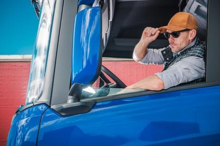 Photo pour Young Caucasian Truck Driver Wearing Baseball Hat Inside Semi Cabin. - image libre de droit