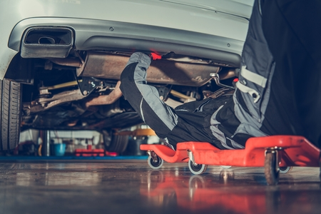 Photo pour Caucasian Vehicle Mechanic in His 30s Repair Vehicle Laying Under Vehicle on the Creeper. Automotive Industry. - image libre de droit