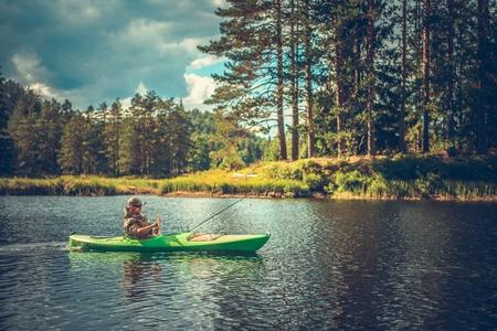Foto de Caucasian Men in His 30s Fishing From a Kayak. Lake Recreation Time. - Imagen libre de derechos