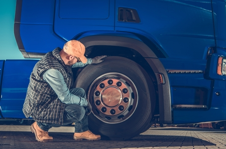 Photo pour Caucasian Driver Checking Semi Truck Wheels Looking For Potential Issues. Transportation Industry Safety. - image libre de droit